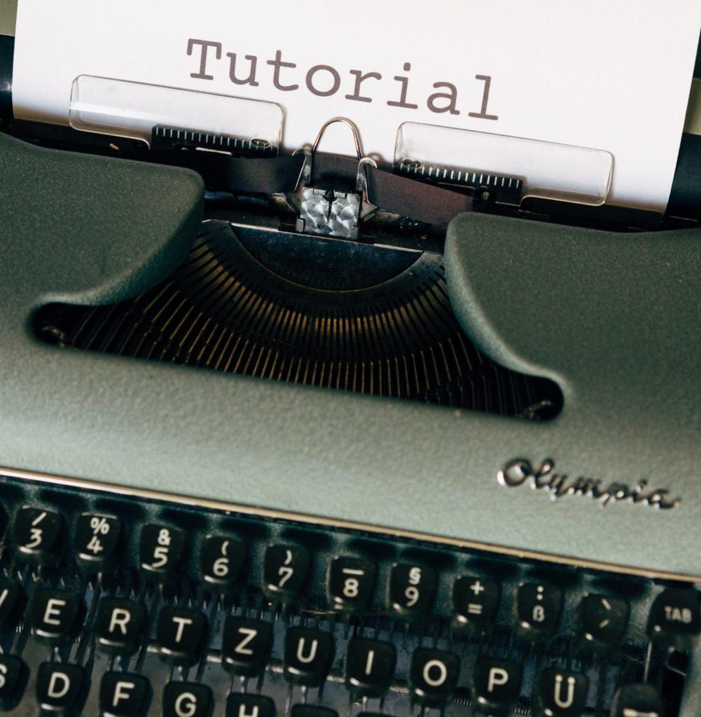 Schreibmaschine mit Papier auf dem Tutorial geschrieben steht